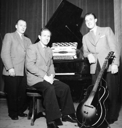 Orkester, tre män med musikinstrument. Till vänster Olle Fransson, dragspel. ( Se även bild OLM-91-102-8291).