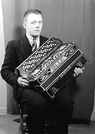 En man med musikinstrument (dragspel). Olle Ljunggren eller Olle Fransson (?). (Se likheten med mannen på bild OLM-91-102-8291, Olle Fransson)