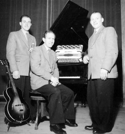 Orkester, tre män med musikinstrument. Till höger Olle Fransson, dragspel. (Se även bild OLM-91-102-8291).