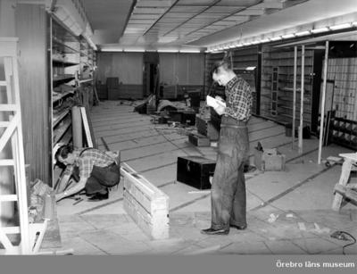 Affärsinteriör, byggnadsarbete (renovering), två män. Oscaria.