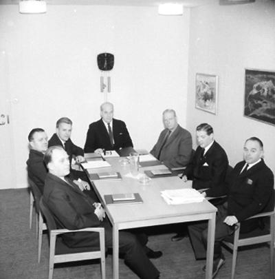 Rumsinteriör, grupp sju män vid bordet. Metalls styrelse på Medborgarhuset.