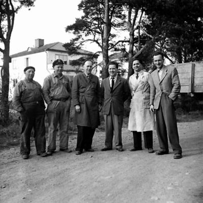 Vretstorpsverken, grupp sex män. Fabriksbyggnader i bakgrunden.