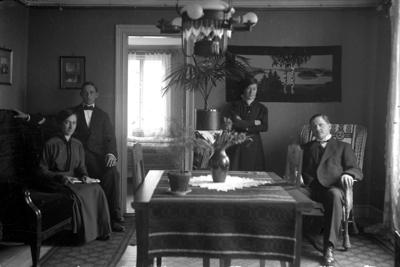 Rumsinteriör, fyra personer. Olga (givarens faster, född Pettersson, gift med Petrus Sjöqvist), Martin Pettersson (givarens farbror), Ester Pettersson (givarens faster), Petrus Sjöqvist (gift med Olga).