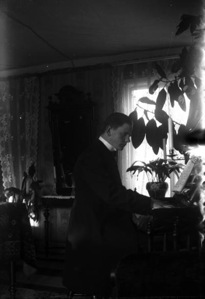 Rumsinteriör, en man vid pianot. Petrus Sjöqvist (gift med Olga Pettersson, givarens faster).