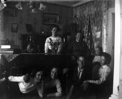 Hemmet på Kungsgatan 33 i Lindesberg. Rumsinteriör, grupp sju personer. Eva Sofia Pettersson (givarens farmor, samt några fastrar och kompisar).