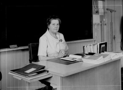 En kvinna vid skrivbordet. Almby skola, klassrumsinteriör. Lärarinna fru Lisa Neijbert-Johansson, avgångsåret.