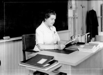 En kvinna vid skrivbordet, läsning. Almby skola, klassrumsinteriör. Lärarinna fru Lisa Neijbert-Johansson, avgångsåret.
