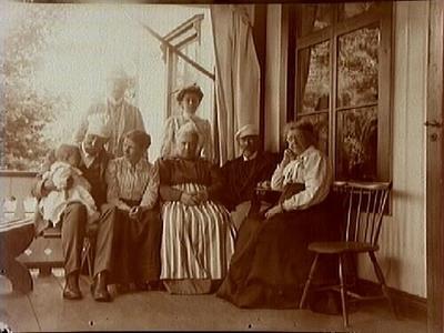 Lerbäcks Prästgård, släktgrupp på veranda. Från vänster sitter Alfred Thermaenius med hustru Gerda, babyn dottern Maj. I mitten modern Jenny Thermaenius, prosten Wilhelm Callmander med fru Anna. De stående troligen Ingrid Toll (född Callmander) med maken Hugo Toll.