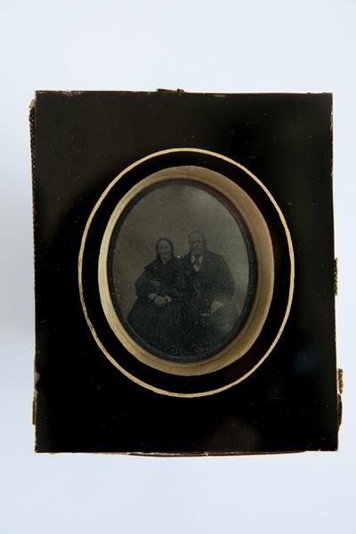 På baksidan av den vänstra bilden står skrivet med blyerts i överkanten: Gottfrids mamma [?]. I nederkanten står med bläck: 18 1/2 år gammal.  På baksidan av den högra bilden står skrivet med blyerts i överkanten: Gottfrids farmor och farfar. I nederkanten står med bläck: Augusti 1861. Edv. Ths.   De båda blyertsanteckningarna ser ut att vara samma handstil och de båda bläckanteckningarna ser ut att vara en annan handstil, sannolikt Edvards.   Edvard var far till Alfred, vars bilder ni har i ert arkiv.  Alfred var Gottfrids storebror. Gottfrid var min farfar. Gottfrids mamma, alltså Edvards hustru, hette Jenny. Hon var född den 18 februari 1843. Då Edvard tog bilden var hon 18 1/2 år, så det var i augusti 1861, samtidigt med bilden på föräldrarna. Edvard och Jenny gifte sig på våren 1867, så när bilden togs var de kanske nykära. Gottfrids farfar och farmor, alltså Edvards far och mor, hette Johan och Eva Sofia.   Famijljen flyttade till Hallsberg 1868. När Edvard tog bilderna bodde han och föräldrarna i Torshälla (eller om det var Eskilstuna, jag kan ta reda på det). Det var alltså inte Örebro län. Men eftersom de här bilderna har nära anknytning till Alfreds bilder, som ni har, vore det naturligt att förvara dem alla tillsammans.   Jag hittade de här bilderna när jag tog reda på min mammas saker. Hon avled i höstas. Mamma och pappa hade många saker från Gottfrid, min farfar. Så de båda bilderna har kommit den vägen till mamma.
