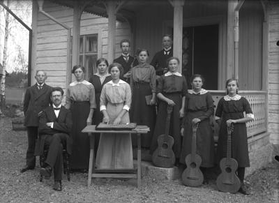 Ullersäters församlings Musikförening, grupp framför byggnad. Längst upp till vänster Johannes Natanael Bäckman. Till höger Svea Falk (?) och Anna Andersson.