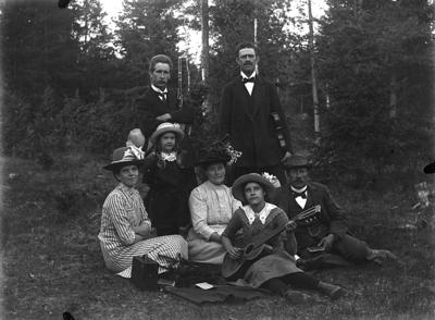 Grupp sju personer. Till vänster familjen Edit och Johannes Natanael Bäckman med dottern Nanna och familjen Fält från Ullersäter med dottern Svea med gitarren.
