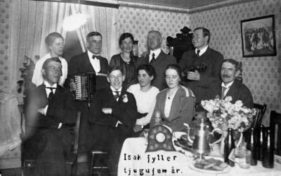 Gråbo, Karlskoga. Rumsinteriör, familjegrupp tio personer, Isak Berggrens 25-årsdag. Övre raden från vänster: Elin Berggren, gift med Karl Berggren, Hilma Svensson (född Berggren), Hjalmar Svensson, Karl Wilhelm Bråthe (med fiol). Nedre raden: Fritz Sjögren, Isak Berggren, Greta Nordmark, okänd, Fritz Sjögrens far. Mannen med fiol är Karl Wilhelm Bråthe, född 1883, filare i Bofors. Han bodde vid denna tidpunkt i Rosendal, nr 604. Han är farfar till Lars Bråthe.