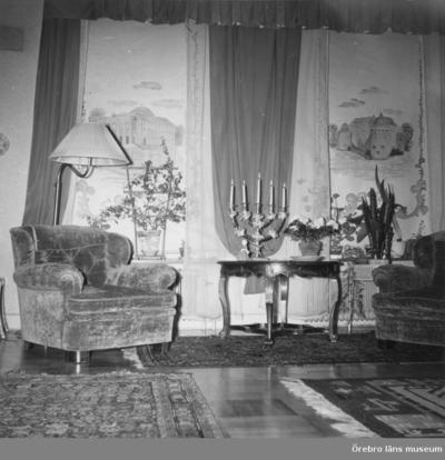Salongen i läkarvillan på Järnvägsgatan 19, Örebro. Huset ägdes av doktor Ragnar Melander (född 1895). I huset bodde också hustrun Elsa Melander (född 1897) och sonen Mats (född 1933). Familjen ägde huset från 1940 till 1974. Rullgardinerna finns i ÖLM:s föremålssamlingar, Inv.nr: 39071_1-3. Rullgardinernas motiv: 1-Örebro slott (tejpad på v. kanten), 2-Konserthuset, 3-Arbetshuset. På alla tre rullgardiner står målarens namn: Truls.   Dnr: 2010.310.175