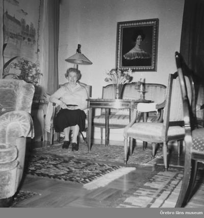 Salongen i läkarvillan på Järnvägsgatan 19, Örebro. Huset ägdes av doktor Ragnar Melander (född 1895). I huset bodde också hustrun Elsa Melander (född 1897) och sonen Mats (född 1933). Familjen ägde huset från 1940 till 1974. Damen på bilden är Elsa Melander. Rullgardinerna finns i ÖLM:s föremålssamlingar, Inv.nr: 39071_1-3 Rullgardinernas motiv: 1-Örebro slott (tejpad på v. kanten), 2-Konserthuset, 3-Arbetshuset. På alla tre rullgardiner står målarens namn: Truls. Se boken