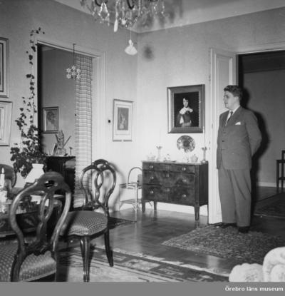Salongen i läkarvillan på Järnvägsgatan 19, Örebro. Huset ägdes av doktor Ragnar Melander (född 1895). I huset bodde också hustrun Elsa Melander (född 1897) och sonen Mats (född 1933). Familjen ägde huset från 1940 till 1974. Mannen i dörröppningen är Mats Melander. Rullgardinerna finns i ÖLM:s föremålssamlingar, Inv.nr. 39071_1-3 Rullgardinernas motiv: 1-Örebro slott (tejpad på v. kanten), 2-Konserthuset, 3-Arbetshuset. På alla tre rullgardiner står målarens namn: Truls. Dnr: 2010.310.175