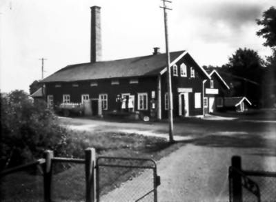Floby mejeri. Hofflanders möbelafär och källaren. Mjölkbilen kördes av Erik Gustavsson. På trappan mejeristen Göran Johansson me fru Signe och sonen Halvard samt en mejerska.