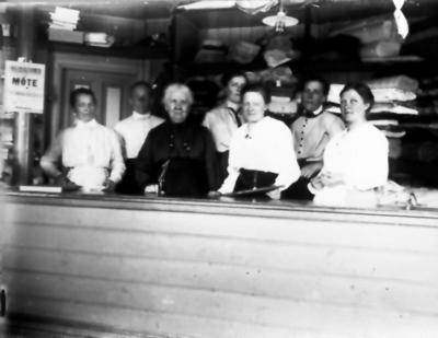 En marknadsdag inne i fröken Aronssons affär omkring 1920. Från vänster Lovisa Petterssonn, Selma Johansson Bråkabo, Frk Carolina Aronsson, Anna på Brännet, Gerda Andersson, Selma Johansson Lund, Gunhild Johansson Lövängen.