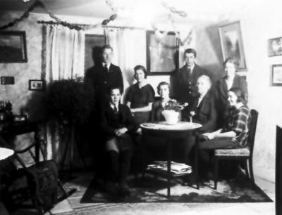 I fanjunkare Claes Levin Ottergrens hem, efter hans död. Claes, Birger, Karin, Britta, Lennart , änkan Ebba Ottergren, Ingrid och Marta. Fanjunkaren på tavlan.