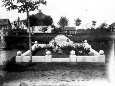 Grav för Frans Andersson och Frida Maria Andersdotter. I bakgrunden kyrkskolan och lärarbostaden. Till höger den gamla fattigstugan som revs 1939.