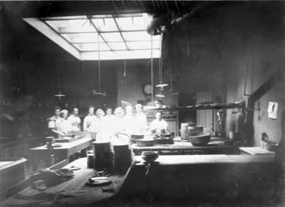 Badrestaurangen, Mösseberg. Byggnaden revs 1961-62, men restaurangrörelsen hade upphört tidigare. Restaurangens kök omkring 1915. Kökspersonal och troligen även elever. Restaurangen hade tre olika matsalar. Kl. 1 för mera välsituerade gäster. Kl. 2 var för inskrivna badgäster, som begärt denna klass samt för läkare och sköterskor. Kl. 3 avsåg personal i parken, baderskor, städerskor och övriga av Sanatoriets personal samt dessutom för s.k. fribadare d.v.s. mindre bemedlade,  vilka fick bad och behandling utan att själva betala.