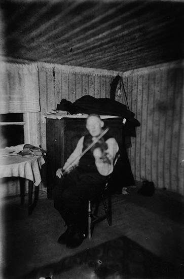 Rumsinteriör, en äldre man spelar fiol. Spelmannen Axel Pettersson, bror till Augusta Olsson (Erik Theon Olssons mamma).