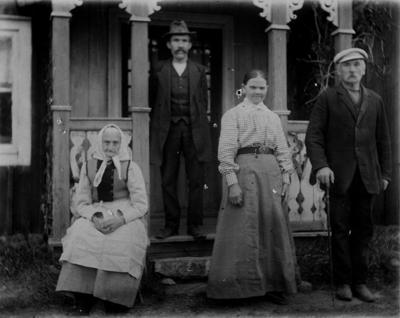 Bostadshus, fyra personer framför huset. Stående på verandan Herman Andersson, nedanför L.J. Juhlin med fru Augusta. Sittande Juhlins mor.