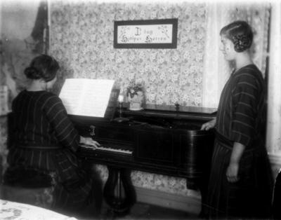 Rumsinteriör, två flickor vid pianot. Erik Theon Olssons döttrar, Thea Elfrida och Linnéa prövar taffeln. Bilden tagen 1928 eller 1929.
