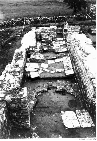 Norra koret från väster. Golvet delvis uppbrutet. Visande i förgrunden norra absiden och vid sidoaltaret (i jämhöjd med pilen) grunden till norra korets äldre östra mur.