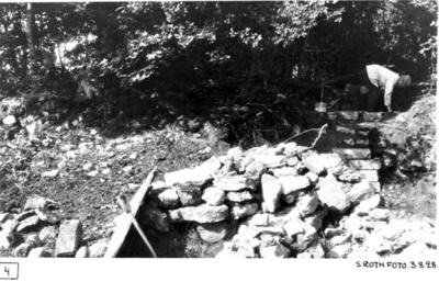 Det första påträffade partiet av klosterkyrkans östmur fr. ö. I förgrunden stenar från schaktet. Oidentifierad man arbetar i bakgrunden.
