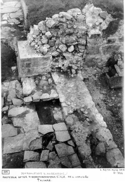 Resterna efter den romanska kyrkans korsarms södra mur från väster uppifrån, altare. Finns här spår efter portal?