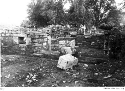 Mittkorets sydmur med öppningarna mot sydkoret. I förgr. stenen nr. 100 i läge som den påträffades framför där den sedan inpassades.