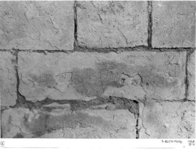 Södra koret. Norra muren. Andra stenen väster om öppningen till mittkoret i andra skiftet från kälskiftet (se foto 22) med i putsen före finslipningen inristade bokstavstecken (R LU).