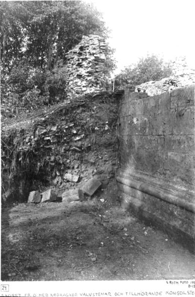Södra koret från öster med nedrasade valvstenar och tillhörande konsolsten in situ på korsets nordmur (vid pinnen).