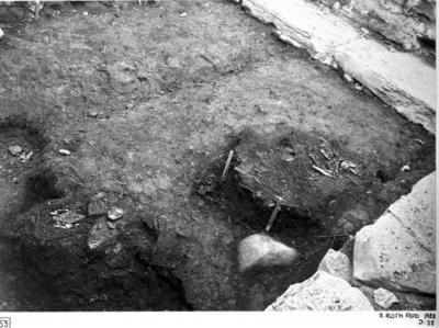 Nordöstra kapellet från sydost. Till vänster järnbeslaget fynd 1928:273 placerat i läge som det påträffades. Till höger trägolv III översta högra hörnet, norra muren och stenar därinvid, i nedersta högra stenar vid östra muren.