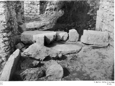 Norra sidoskeppet. Partiet mellan östligaste pelaren i mittskeppets nordmur och sidoskeppets nordmur. Stenarna i läge som de påträffades. Stenblocken i förgrunden med solfläckar. Tympanonsten.