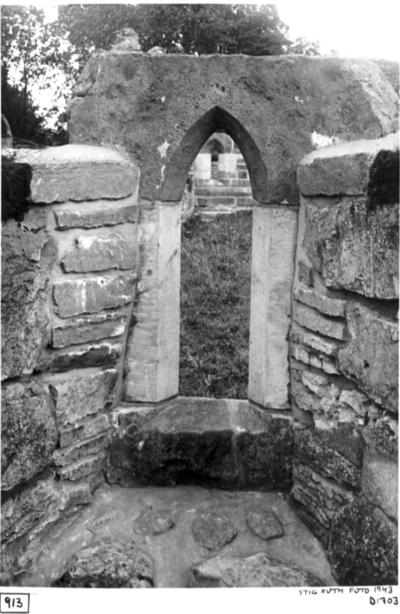Norra korsgångens sydmur. Insidan. Östra fönstret återuppsatt, genom fönstret skymtar det återuppsatta fönstret i södra korsgången. Från norr.
