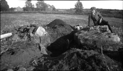 Utgrävning av stenåldersgrav. Hällkista med skålgropar å takblock. Fynd: benbitar, bärnstenspärlor, kvarssten, delar av lerkärl, sekundär grav från järnåldern.