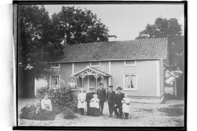 En och en halvplans bostadshus med veranda i snickarglädje. 9 personer framför huset. Aug. Andersson (Reproduktion 1934)