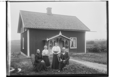 Envånings bostadshus med inredd vind, veranda med snickarglädje. Fyra personer framför huset. P. F. Johansson