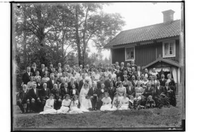Bröllop, brudpar och bröllopsgäster. Tvåvånings bostadshus med veranda med snickarglädje. Saxén