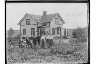 En och en halvvånings vinkelbyggt bostadshus med glasad veranda och förstuga. Familjegrupp 9 personer framför huset. August Persson.