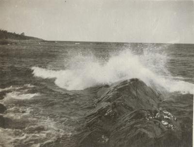 Naturbild på havet med kraftiga vågor som slår mot strandklippor.