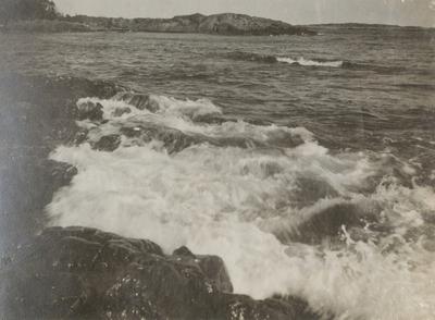 Naturbild på havet med vågor som slår mot strandklippor.