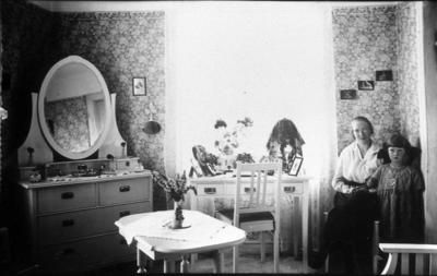 Interiör från Karl Perssons i Lugarp. Karls syster Karin var förestånderska för ålderdomshemmet i Timmele. Barnet troligen en sommarflicka.