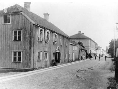 Brahegatan i Gränna från söder. Närmast nuvarande Brahegatan 37 med apoteksskylt ovanför dörren. En grupp unga och äldre står mitt i gatan.
