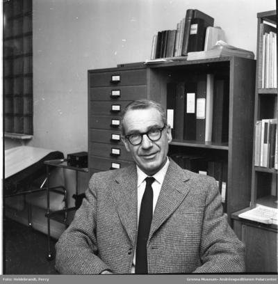 Porträtt av doktor Arne Otto Kinch, i kavaj och slips, på Provinsialläkarmottagningen i Gränna. En brits i bakgrunden till vänster samt skåp och hyllor till höger.