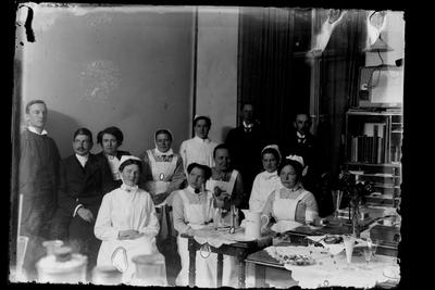 Hålhults sanatorium, interiör, gruppbild, personal, uppvaktning? femte från vänster stående syster Rut Larsson 1/7 1914 -> tredje från vänster sittande Hanna Johansson kökförest. 15/2 1913