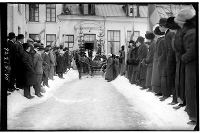 Hålahults sanatorium, exteriör, tvåhjulig öppen vagn, häst och vagn framför porten, snö på marken, två granar vid port, flaggor, mycket folk på båda sidor av gången