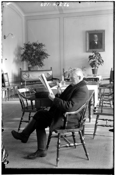 Hålahult sanatorium, interiör, gammal man sitter och läser tidningen med ett förstoringsglas, i matsalen? Klädd i vinterrock och läderstövlar