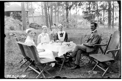 Hålahult sanatorium, exteriör, tre kvinnor i uniform och en man runt ett kaffebord i naturen, manen underläkare J.B. Sundström 1/7 1915 - 15/8 1915